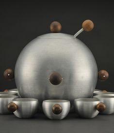 Russel Wright's circa 1935 aluminum-and-walnut punch bowl with 12 cups