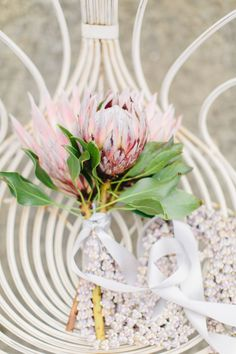 Wrapped in a strand of seashells: http://www.stylemepretty.com/2015/08/28/spotted-in-the-vault-this-week-blush-pink-protea/