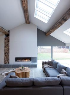 Scandinavian inspired living room with vaulted ceilings, exposed wooden beams, corner windows, built-in fireplace, dark gray sectional and space for firewood | Janey Butler Interiors