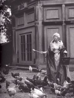 Deborah Cavendish nee Mitford, then Duchess of Devonshire, feeding her chooks in a silk taffeta ballgown and wrap, bucket, farm spoon, a twinkle in her eye and a modest complement of family jewels at the family seat, Chatsworth House,