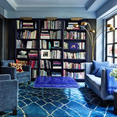 In the library of accessories designer Fiona Kotur's Hong Kong home, the pair of Christian Liaigre armchairs and the custom-made sofa and its pillows are all covered in Manuel Canovas fabrics; the cocktail table is by Yves Klein, while the Moroccan carpet from Woven Accents and the floor lamp in the corner are both vintage. Brass picture lights by Ralph Lauren Home top the bookshelves.