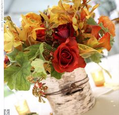 Tables held large, low centerpieces of flowers, including Hocus Pocus roses, saffron-hued cymbidium orchids, orange Mokara orchids, speckled tiger orchids, mango calla lilies, orange ranunculuses, green geranium leaves, and croton leaves.