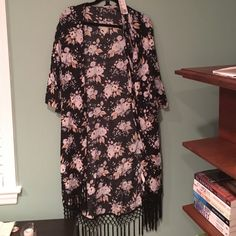 A floral kimono with fringe on the bottom This is a black, blue and white kimono with black fringe on the bottom. Never worn and from forever 21. Goes to back of knees and has mid length sleeves Forever 21 Sweaters Cardigans