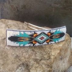A beautiful Native American-inspired beaded hair barrette is the perfect gift for anyone with long hair that needs a unique hair accessory to keep it out of her face. This white beaded hair clip is created from a gorgeous Native American bead loom pattern.  * Feather and geometric bead pattern isdone in primary colors with a white background. * Measures approximately 5 X 1 1/4 (12.7 cm X 3.175 cm) * Animal  Vegan-friendly with a faux leather backing * Quick release barrette clip  *******...