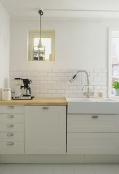 I like the clean, simple look of the white subway tiles and cabinet, with the more traditional porcelain sink and wooden/butcher block counter