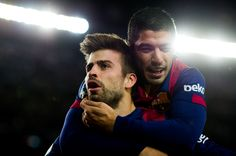 Gerard Pique (L) of FC Barcelona celebrates with his teammate Luis Suarez after scoring his team's third goal during the La Liga match between FC Barcelona and RCD Espanyol at Camp Nou on December 7, 2014 in Barcelona, Catalonia.