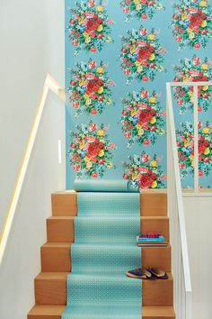 A flamboyant wallpaper design featuring a large scale floral repeated motif, with a stylised hand painted effect.