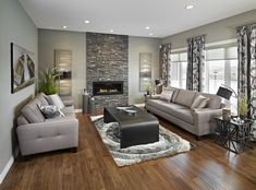 Pairing the linear fireplace with cultured stone gives traditional stone material an modern twist. This living room also features rustic hickory hardwood flooring - Yellowstone Park Royale II Show Home