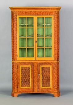 Pennsylvania painted two part corner cupboard, early 19th c., retaining a vibrand ochre sponge decorated surface with yellow doors.