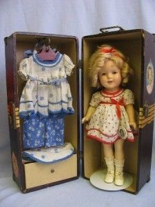 Shirley Temple doll with trunk and costumes, c. 1934. The red-dotted dress is like her costume in 'Baby Takes a Bow', and the blue dotted dress with matching bonnet is from 'Curly Top'. There's also a set of floral-print beach pajamas.