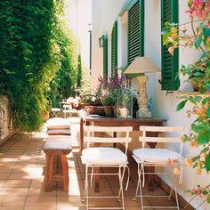 Patio con mesa de madera, sillas de metal plegables, banquetas, suelo de terrazo, ventanas verdes y plantas