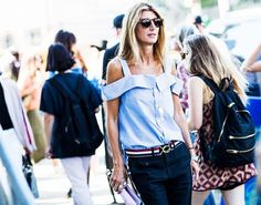 A cut-out-shoulder striped top is paired with belted trousers and classic sunglasses