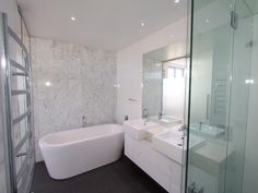 Black floor tiles, white/grey marble feature wall tiles, white vanity
