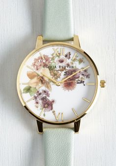No matter the weather, you enjoy a lovely look accessorized with this charming Olivia Burton Flower Show watch! An arrangement of blooms in muted tones pattern the face of this gold watch, while a mint leather band makes it versatile enough to don again and again.