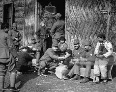 Occupying Japanese soldiers with Chinese children at whose cottages they are lodged.