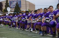 The entire Garfield High School football team kneels during national anthem before their game against West Seattle tonight. (Photo courtesy of Seattle Times/Dean Rutz)