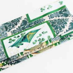 "Ireland Forever Cotton Napkins (Set of 4) ME2Designs Handmade Table Decor. The handmade Ireland Forever! napkins feature a green & cream background with two different antique damask designs, Gaelic script in gold, and Gaelic sheet music. There are images of these four antique postcards scattered around the print: 1 - a St. Patrick's Day Greetings with a large Irish harp, an American flag, and a horseshoe with shamrocks and ""Wishing You Luck""; 2 - a postcard image that has Ireland Forever!..."