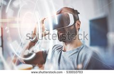 Bearded man wearing virtual reality glasses in modern interior design coworking studio. Smartphone using with VR headset. Horizontal,flares effect, blurred background