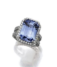 SAPPHIRE AND DIAMOND RING.  The emerald-cut sapphire weighing 13.46 carats, framed by small round diamonds, additional diamonds all around the double band, weighing approximately 3.25 carats, mounted in platinum