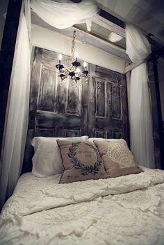 2 old doors re-purposed as a head board. This whole scene is dramatic & lovely.