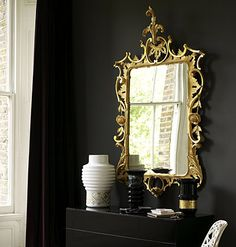 Set a gilt mirror against black to really let the flourishes stand out. Coupled with modern mosaic touches, this combination becomes an instant design classic.