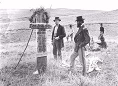 Photograph taken in 1879 during U.S. Army re-burial visit to the Custer batcitlefieldThe expedition was led by Captain George K. Sanderson, seen here in the foreground looking at the recently erected monument to Myles Keogh and the fallen members of Company I, 7th US Cavalry.""