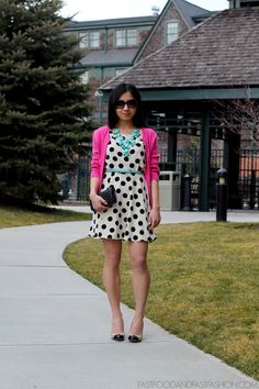 White polka dot dress with a pink sweater and turquoise accessories.