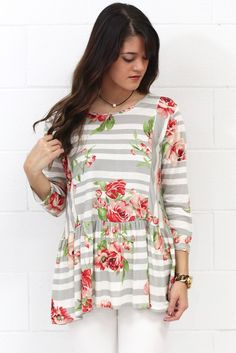 Perfectly mixed prints... stripes and floral! Three quarter length sleeves with a relaxed dropped waist like a peplum. Grey and white stripes with floral patter in rose, red, and green.