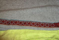 Embroidered decoration on the bottom edge of an apron-dress. The strip of red wool is stitched to the dress using an Ösenstitch in blue and brown yarn. The front portion is decorated with a pattern of connected rings inspired by metalwork embroidery from Oseberg. By Brynja.