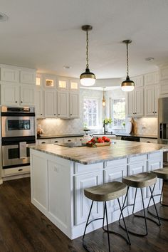 A kitchen remodel filled with white cabinets, warm wood tones, a marble backsplash, and gorgeous granite countertops.