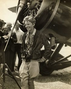 American aviator Amelia Earhart (1898-1937), smiling as she stands near her plane sometime in the 1930s.