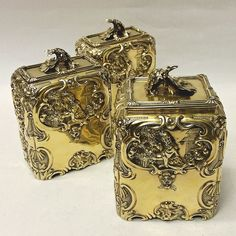 Antique George II Silver Caddies by FREDERICK VONHAM - 1759 n excellent quality matching set of antique sterling silver tea jars with chinoiserie decoration and original deep gilt finish. After a Paul de Lamerie design. The matching pair of rectangular caddies (for green and black tea) have sliding tops, the larger square sugar box has a hinged lid. Cast silver flower finials. The deep embossed and engraved decoration is particularly attractive; each caddy has a front and back panel…
