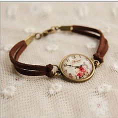 """TEA TIME Vintage Inspired Floral Watch Style Bracelet with Leather bracelet style band. This Vintage inspired bracelet watch has antique finish, gold bezel and Antique Gold style closure. Watch out, it's not a watch. The watch is non-working and just for look and fun, so you are not pressed for time! It is always a TEA TIME when you wear this one! So RELAX and enjoy your Tea. Details: - Play watch style bracelet with glass top and real hands. - Belt fits from 7.5"""" to 8"""" wrists. - Meant to be…"""