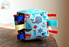 Sailing by the stars nautical-theme soft taggie block toy for baby on-the-go by Iris Says #handmade #toy #taggie #ribbons #nautical #whale #sailboat #fish #anchor #stars #stripes #banner #bunting #flags #fun #sensorytoy #traveltoy #minky #turquoise #red #blue #yellow