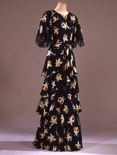 1930-1932 Long dress in crêpe de rayon, printed in motif of horse chestnut leaves and flowers in different colors on blue background; Italian.