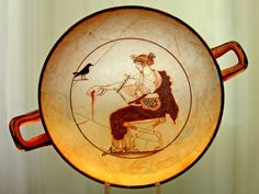A kylix depicting the God Apollo pouring a libation and holding an early version of the Lyre (chelys) which was made from the shell of a tortoise. The bird may represent the crow which announced the marriage of the nymph Aigle-Korone, the daughter of King Phlegyas. Provenance: Delphi, 480-470 BCE, artist unknown. (Delphi Archaeological Museum).
