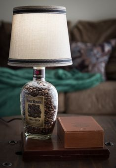 This cool table top lamp was hand made out of a repurposed Four Roses whiskey bottle and repurposed cigar boxes. The cigar box base and all others function as a storage compartment. The base is opened by tilting the lamp back. The bottle and cigar boxes are attached to the wood