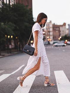 White maxi dress with cutouts, black purse, & lace up box heel sandals