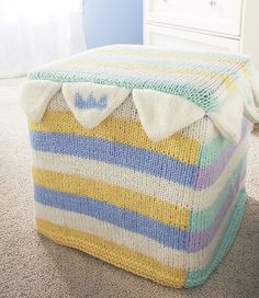 Free knitting pattern for Crown Point Ottoman Cover - Julie Farmer designed this colorful fun cover for Red Heart that's perfect for a nursery or child's room. 15 x 15 x 15