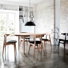 Dining room with exposed brick wall, cement floors and wishbone chairs