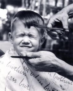 A young Kurt D. Zwikl has his hair cut at the department store's barbershop while being photographed by dad, William R. Zwikl.