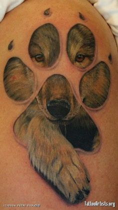 tattoo wolf coming through a paw print