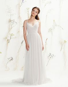 Spaghetti straps adorn this soft English net A-line gown featuring a V-neckline with beaded trim at the natural waistline and a deep criss-cross back. A feminine and ethereal wedding day look. To see more of our dresses, follow us! @mycouturebridal