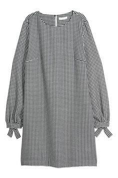 Krótka tkaninowa sukienka z okrągłym dekoltem. Długie rękawy z wąskim mankietem i wiązaniem, kieszenie po bokach. Na karku rozcięcie z guzikiem, karczek z k