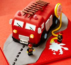 Fire engine cake. Stun a crowd and get creative with this themed celebration cake - details include a chocolate ladder, icing water splash and toy firemen.
