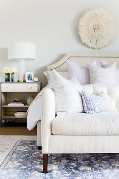 Luxe bedroom with an upholstered linen headboard, a JuJu hat, and throw pillows