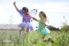 Yooniq images - Girls (7-9) wearing fairy costumes running in meadow