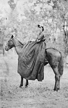 1865.  A woman riding a horse sidesaddle. She is wearing a very long riding habit.