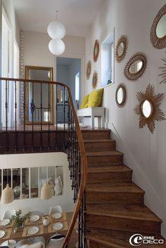 La cage d'escalier de la maison de Florence Bouvier est décorée d'une collection de miroirs soleil en rotin vintage chinés aux Puces du Canal à Villeurbanne