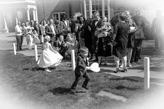 Children play and the guests relax after the wedding ceremony. Bride & groom getting married outside in traditional style at Theobald's Park Hotel North London.